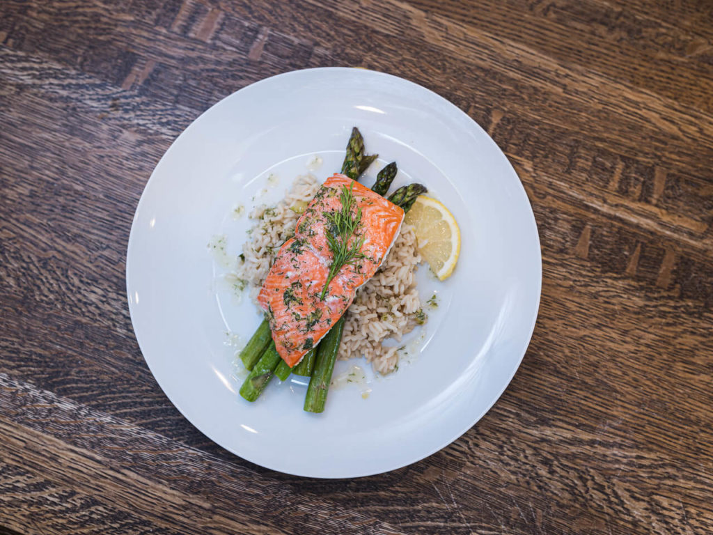 salmon on bed of asparagus and rice